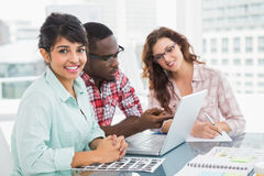 Cheerful coworkers speaking and using laptop Royalty Free Stock Photo