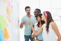 Cheerful coworkers standing and speaking together Stock Photography