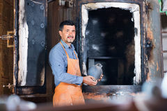 Cheerful craftsman carrying fresh baked black glazed vessel Stock Photo