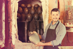 Cheerful craftsman carrying fresh baked black glazed vessel Stock Images