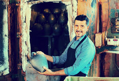 Cheerful craftsman carrying fresh baked black glazed vessel Royalty Free Stock Images