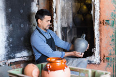 Cheerful craftsman carrying fresh baked black glazed vessel Royalty Free Stock Photo