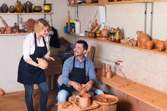 Cheerful craftsman talking to woman in workroom Stock Photography