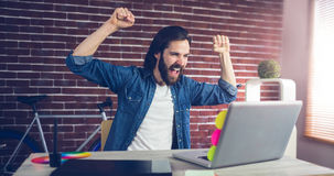 Cheerful creative businessman with arms raised looking at laptop. In office Royalty Free Stock Image