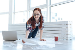 Cheerful creative engineer working on a project. Plan of a new building. Cheerful creative nice engineer holding a drawing and looking at it while working on a Royalty Free Stock Photography