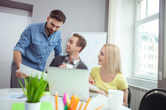 Cheerful creative team is discussing their work. Attractive young men is consulting with his colleagues about his project. He is standing and showing a document Royalty Free Stock Image