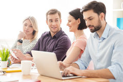 Cheerful creative team is discussing their work. Skillful four young colleagues are talking about a project. They are sitting at desk and smiling. Man is holding Royalty Free Stock Photos
