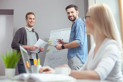 Cheerful creative team is working with joy. Skillful young colleagues are discussing new project. The men are standing near the board and writing notes. Woman is Stock Image