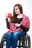 Cheerful crippled lady on wheelchair. Disability drink relax leisure concept. Cheerful crippled lady on wheelchair. Smiling disabled girl holding red cup Stock Images