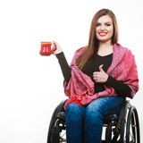Cheerful crippled lady on wheelchair. Disability drink relax leisure concept. Cheerful crippled lady on wheelchair. Smiling disabled girl holding red cup Stock Photo