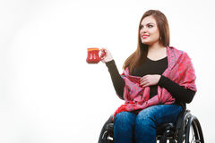 Cheerful crippled lady on wheelchair. Disability drink relax leisure concept. Cheerful crippled lady on wheelchair. Smiling disabled girl holding red cup Royalty Free Stock Photo