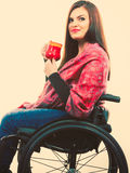 Cheerful crippled lady on wheelchair. Disability drink relax leisure concept. Cheerful crippled lady on wheelchair. Smiling disabled girl holding red cup Royalty Free Stock Photos