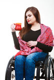 Cheerful crippled lady on wheelchair. Disability drink relax leisure concept. Cheerful crippled lady on wheelchair. Smiling disabled girl holding red cup Royalty Free Stock Image