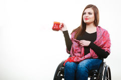 Cheerful crippled lady on wheelchair. Disability drink relax leisure concept. Cheerful crippled lady on wheelchair. Smiling disabled girl holding red cup Stock Image