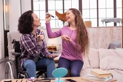 Cheerful crippled woman and girl having fun during makeup. Makeup process. Joyful crippled women using cosmetics while laughing with daughter Stock Photo