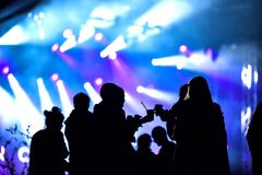 Silhouette of friends socializing at a festival. Cheerful crowd partying at a concert. Silhouette of friends socializing at a festival. Stage lights in the Royalty Free Stock Photos