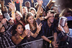 Cheerful crowd photographing performer at nightclub. During music festival stock images