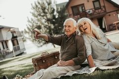 Cheerful curious mature husband and wife having picnic Royalty Free Stock Photos