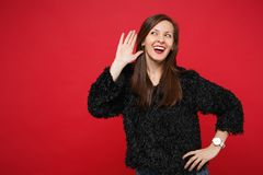 Cheerful curious young woman in black fur sweater eavesdrop with hearing gesture near ear isolated on bright red. Background in studio. People sincere emotions royalty free stock photo