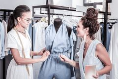 Cheerful curly fashion designer giving some orders her dark-haired trainee. Orders for trainee. Cheerful curly fashion designer giving some orders her dark stock photography