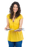 Cheerful curly haired brunette reading magazine Royalty Free Stock Photos