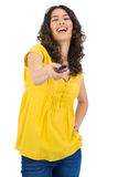 Cheerful curly haired pretty woman changing channel with remote Stock Images