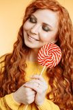 Cheerful curly redhead woman holding a red white lollipop royalty free stock image