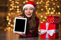 Cheerful curly young female lying and showing tablet blank screen Royalty Free Stock Photography