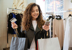 Cheerful curly young lady holding debit card and phone Stock Image