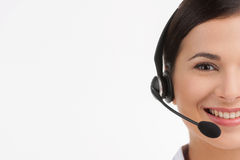 Cheerful customer service representative. Portrait of beautiful young female customer service representative in headset looking at camera and smiling while Royalty Free Stock Photos