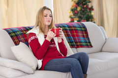Cheerful cute blonde sitting on couch holding mug Royalty Free Stock Photography