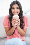 Cheerful cute brunette sitting on couch holding disposable cup Stock Image
