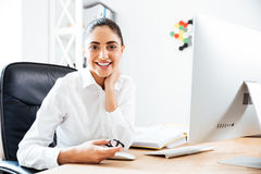 Cheerful cute businesswoman sitting at workplace with computer Stock Photography