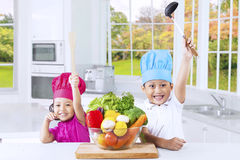 Cheerful cute children ready to cook Royalty Free Stock Images