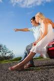 Cheerful cute couple sitting on their cabriolet car hood Stock Photos