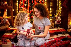 Cheerful cute curly little girl and her older sister exchanging gifts. royalty free stock photos