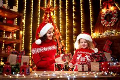 Cheerful cute little girl and her older sister exchanging gifts. royalty free stock photos