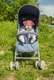 Cheerful cute girl in a pink scarf walks in a blue stroller. Baby girl 9 months legs chatting sitting in a summer carriage Little. Smiling child in a hat on a royalty free stock images