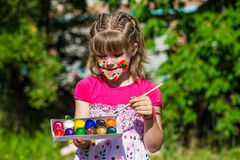 Cheerful cute girl playing with bright paints in the park Stock Photography