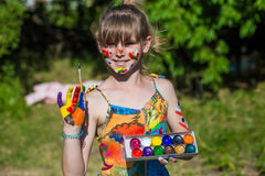 Cheerful cute girl playing with bright paints in the park Stock Images