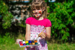 Cheerful cute girl playing with bright paints in the park Stock Photos