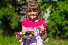 Cheerful cute girl playing with bright paints in the park Royalty Free Stock Images