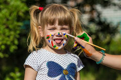 Cheerful cute girl playing with bright paints in the park Royalty Free Stock Photos