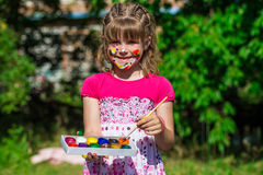 Cheerful cute girl playing with bright paints in the park royalty free stock image