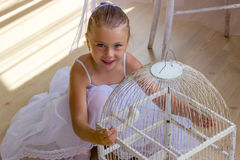 Cheerful cute girl sitting in the floor with bird in cage Stock Photography