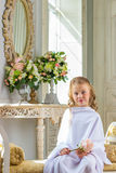 Cheerful cute girl sitting with rose, little angel. In studio Stock Photography