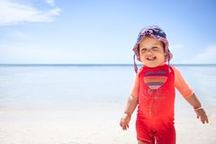 Cheerful cute happy smiling baby kid sun protective suit beach blue sea sky sunscreen background copy space Stock Images