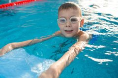 Positive little boy swimming with kickboard stock images