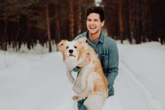 Cheerful cute laughing and smiling guy in jeans clothes with dog border collie red on his hands in snowy forest. concept stock image