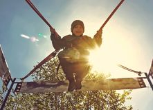 Cheerful cute little boy jumping on a trampoline against the blue sky stock photography
